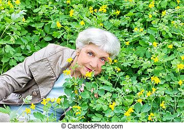 Happy beautiful elderly woman sitting on a glade