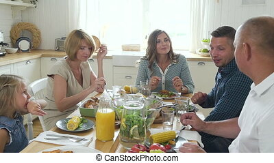 Happy beautiful family eating and talking sitting at table in kitchen room.