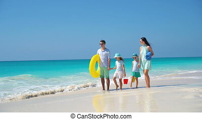 Happy beautiful family of four on a tropical beach vacation