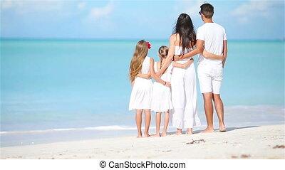 Happy beautiful family on white beach - Back viea of family...