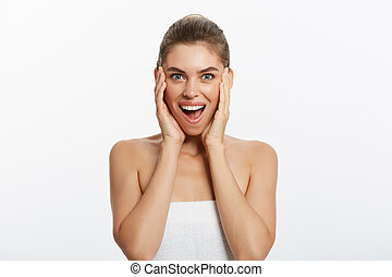 Happy beautiful girl holding her cheeks with a laugh looking to the side. Expressive facial expressions .Cosmetology and Spa