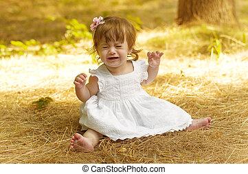 Happy beautiful girl in dress in green garden