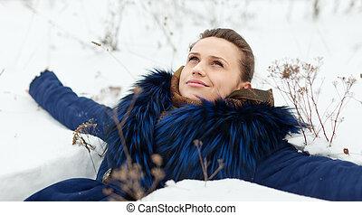 beautiful girl lying down on snow