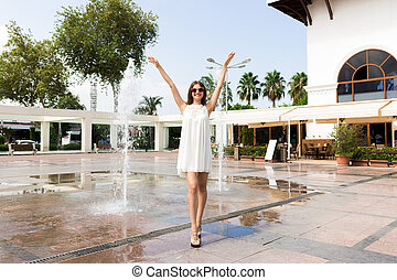 Happy beautiful girl standing near the spray of water and holding hands up
