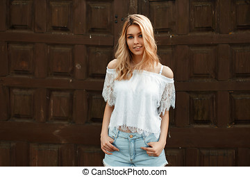 Happy beautiful girl with a smile in a trendy white lace T-shirt with jeans on the street near a wooden wall