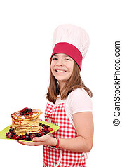 happy beautiful little girl cook with pancakes