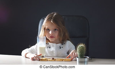 Happy beautiful little girl having a snack with milk and cookies