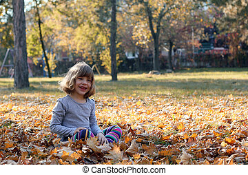 happy beautiful little girl in autumn park