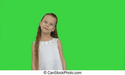 Happy beautiful little girl posing to a camera on a Green Screen, Chroma Key