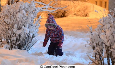 Happy beautiful little girl throws snow in winter, night lighting