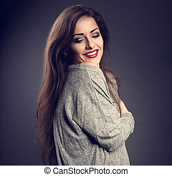 Happy beautiful makeup woman hugging herself with natural emotional enjoying face and toothy smiling on grey background. Closeup toned portrait