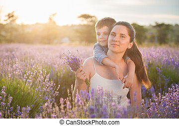 happy beautiful mother and child on the lavender field at sunset