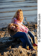 Happy beautiful mother and her daughter having fun on the rocky beach at sunset.