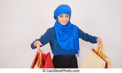 Happy Beautiful muslim woman holding shopping bags -...
