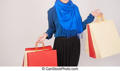 Happy Beautiful muslim woman holding shopping bags -...