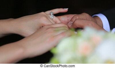 Happy beautiful newlyweds softly holding hands close up on black background. Wedding bouquet on foreground