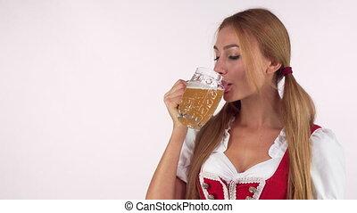 Happy beautiful Oktoberfest woman drinking beer, smiling to...