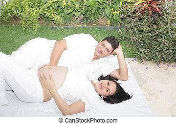 Happy beautiful pregnant woman with his husband outdoors