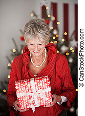 Happy beautiful senior with a Christmas gift - Happy...