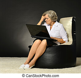 Happy beautiful senior woman with laptop