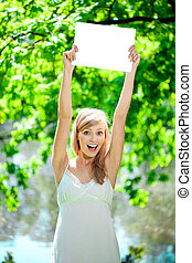 Happy beautiful smiling woman with blank poster  outdoors