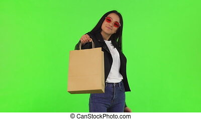 Happy beautiful stylish woman holding out shopping bag to the camera