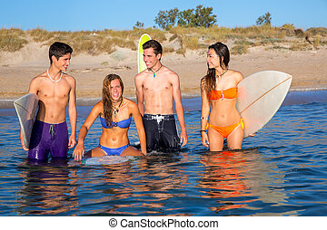 Happy beautiful teen surfers enjoying on beach
