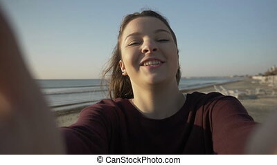 Happy beautiful teenager girl taking selfie using smartphone...