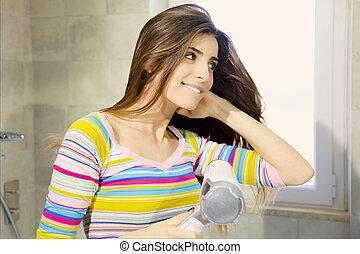 Happy beautiful woman blow drying long hair in bathroom