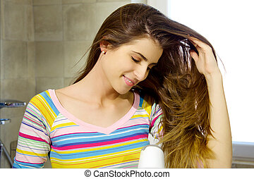 Happy beautiful woman blow drying long hair in bathroom moving with hand