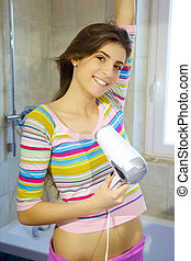Happy beautiful woman blow drying long hair in bathroom smiling looking camera