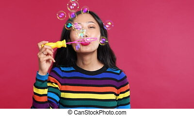Happy beautiful woman blowing soap bubbles isolated over ...