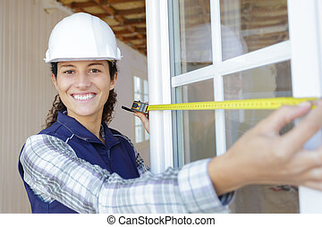happy beautiful woman builder with tape measure
