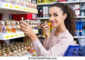 Happy beautiful woman choosing fragrance