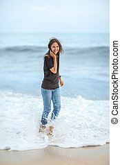 happy beautiful woman enjoying the waves on the tropical sea
