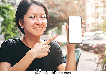Happy beautiful woman holding and showing mobile phone with blank white screen in cafe