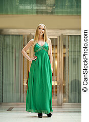 Happy beautiful woman in a long green dress