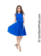 Happy beautiful woman in blue dress posing in studio isolated on white background