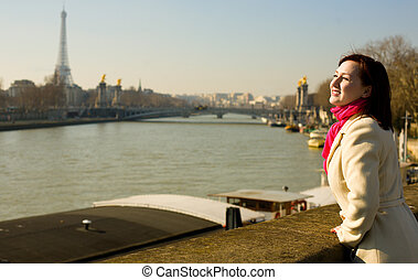 Happy beautiful woman in Paris on the Seine embankment