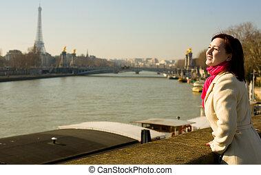 Happy beautiful woman in Paris on the Seine embankment