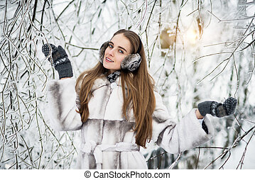 Happy beautiful woman in the winter forest