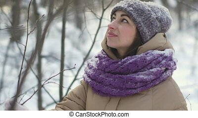 Happy beautiful woman is walking in the winter forest during a snowfall
