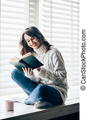 Happy beautiful woman reading book sitting on window sill at home. Relax concept