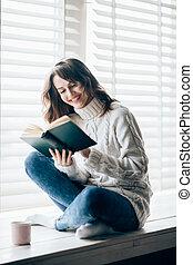 Happy beautiful woman reading book sitting on window sill