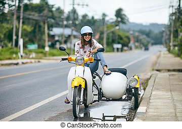 Happy beautiful woman sitting on a retro motorbike