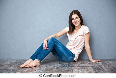 Happy beautiful woman sitting on the floor