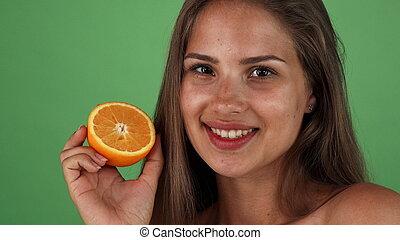 Happy beautiful woman smiling joyfully, holding an orange