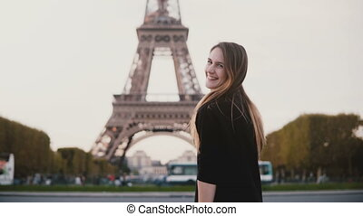 Happy beautiful woman standing near the Eiffel tower in Paris, France. Girl smiling and sending the blow kiss at camera.