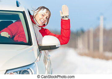 Happy beautiful woman travels by car in winter. - Young...