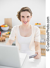 Happy beautiful woman using her notebook for home shopping sitting in kitchen at home